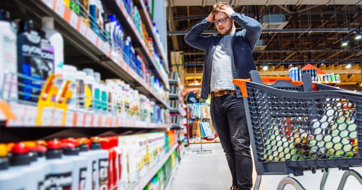 Entscheidungsmüdigkeit bei Eltern: Vater steht vor dem Regal und weiß nicht, was er kaufen soll